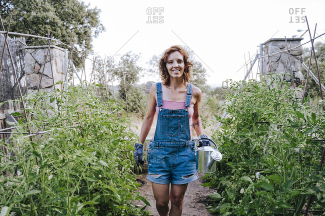 Smiling woman holding watering can while standing amidst plants in vegetable garden