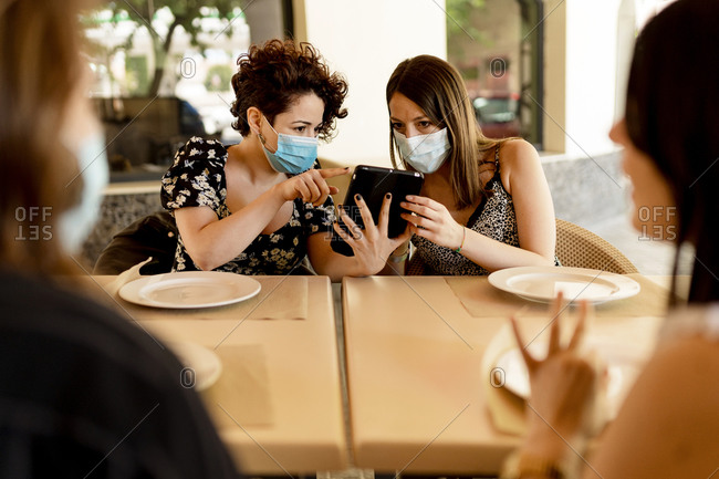 Women wearing masks while sharing digital tablet sitting with friends at table in restaurant