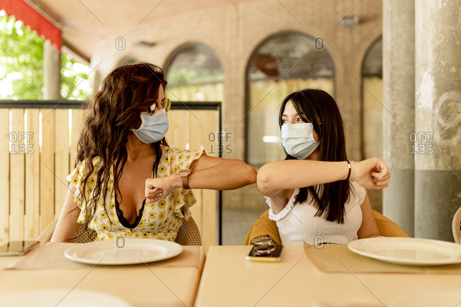 Young women wearing masks while greeting with elbow bump in restaurant