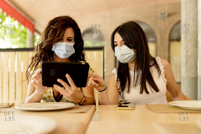 Young women sharing digital tablet while sitting in restaurant during coronavirus