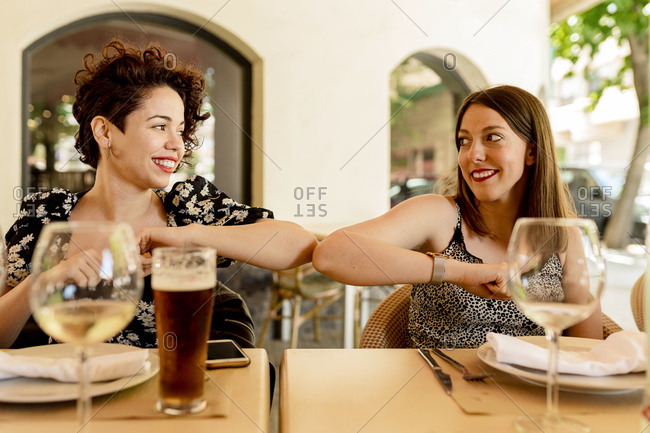Smiling beautiful young women greeting with elbow bump while sitting at restaurant