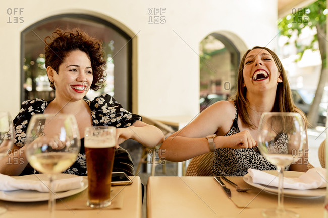 Cheerful young women greeting with elbow bump while sitting and enjoying  at restaurant