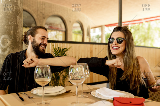 Happy young man and woman giving elbow bump while sitting at table in restaurant