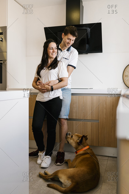 Man embracing woman while looking at dog sitting on floor in kitchen