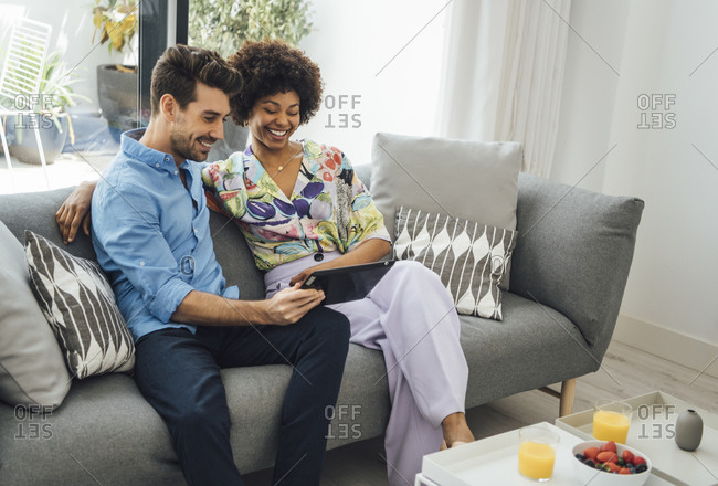 Happy couple using digital tablet while sitting on sofa in living room of penthouse
