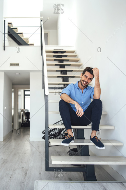 Happy man sitting on floating stairs in modern penthouse