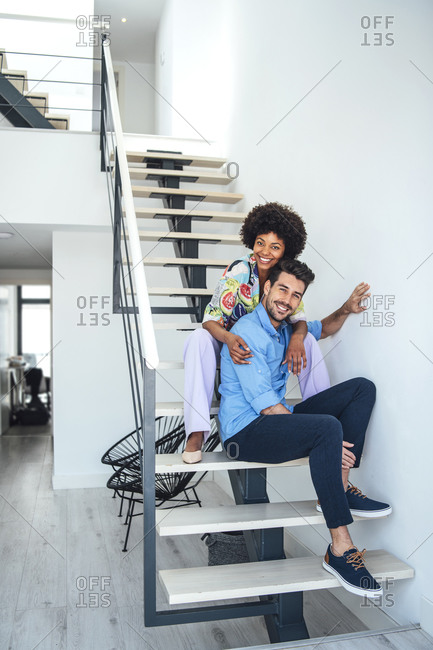 Happy couple sitting on floating stairs in modern penthouse