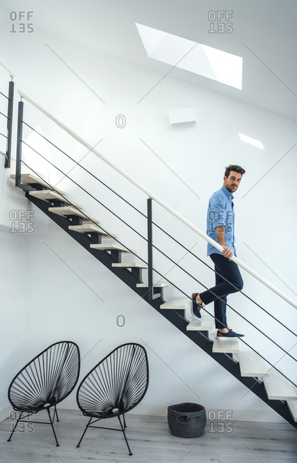 Mid adult man moving down floating stairs in modern penthouse