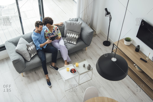 Multi-ethnic couple using digital tablet while sitting on sofa in living room of modern penthouse