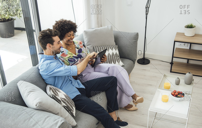 Happy couple using digital tablet while sitting on sofa in penthouse