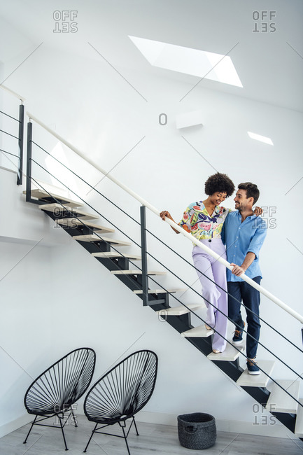 Affectionate couple standing on floating stairs in modern penthouse