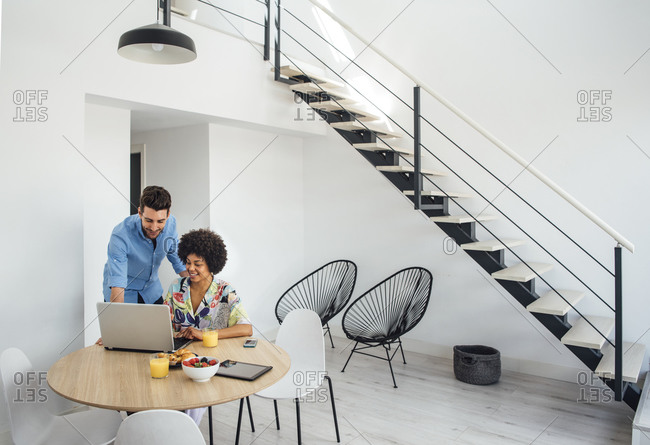 Multi-ethnic couple using laptop at dining table in modern penthouse