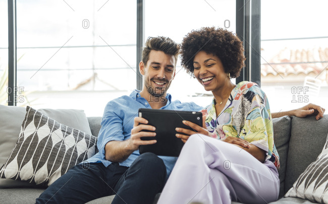 Happy multi-ethnic couple using digital tablet while sitting on sofa in penthouse