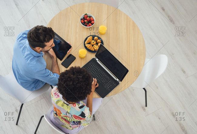 Happy couple using laptop and digital tablet at dining table in penthouse