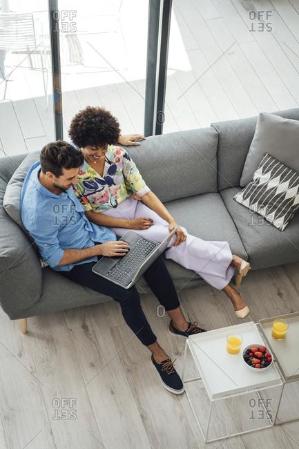 Multi-ethnic couple using laptop while sitting on sofa in penthouse