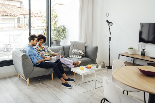 Multi-ethnic couple using laptop while sitting on sofa in modern penthouse