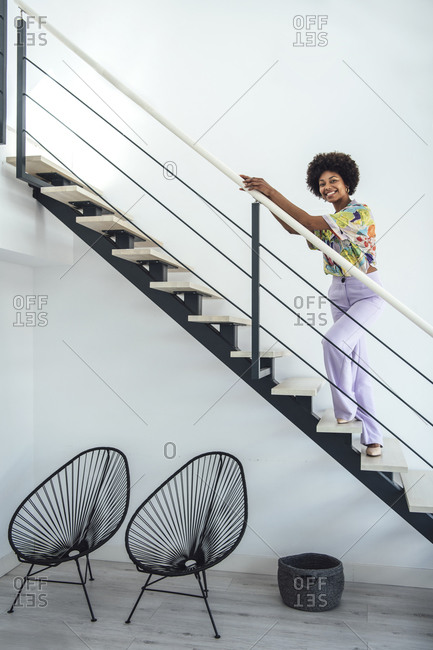 Happy woman standing on floating stairs in modern penthouse