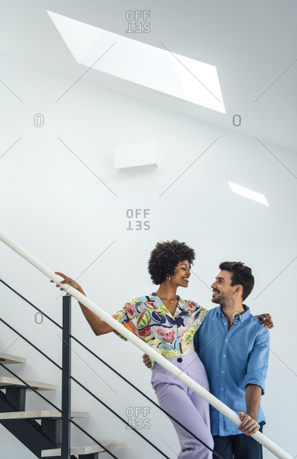 Affectionate multi-ethnic couple standing on floating stairs in modern penthouse