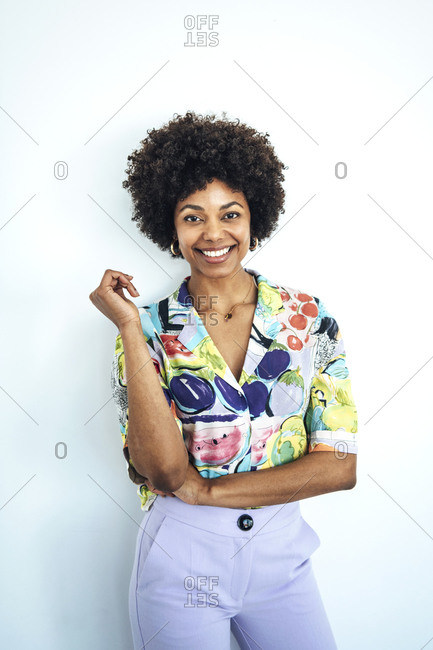 Happy mid adult woman with afro hairstyle standing against white background