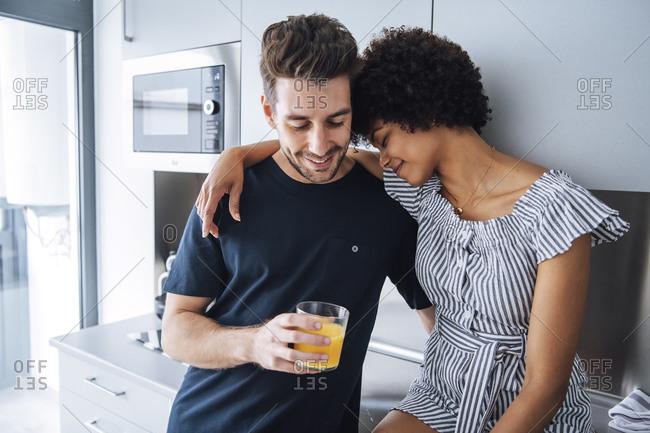 Romantic multi-ethnic couple in kitchen of penthouse