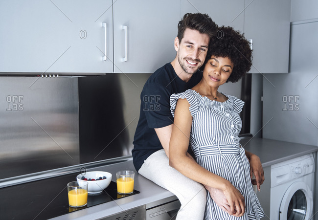 Affectionate multi-ethnic couple in modern kitchen of penthouse