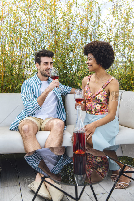 Happy multi-ethnic couple having red wine while sitting on sofa at penthouse patio