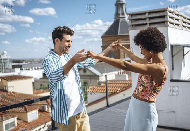 Happy multi-ethnic couple dancing on penthouse patio during sunny day