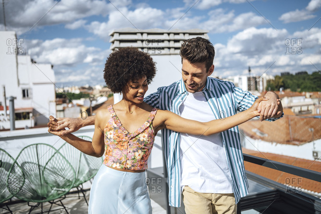 Multi-ethnic couple dancing on penthouse patio during sunny day