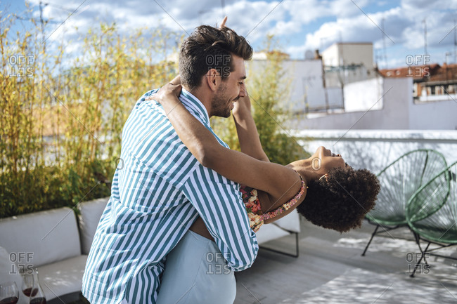 Cheerful multi-ethnic couple dancing on penthouse patio during sunny day