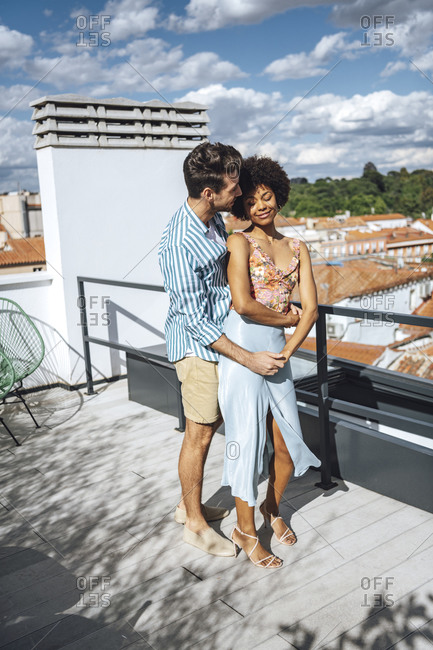 Romantic multi-ethnic couple embracing on penthouse patio during sunny day
