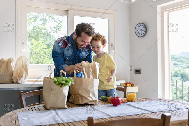 Smiling man showing groceries to son in kitchen at home