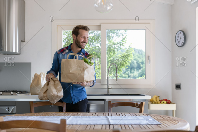 Smiling handsome man holding groceries bag while looking away in kitchen at home