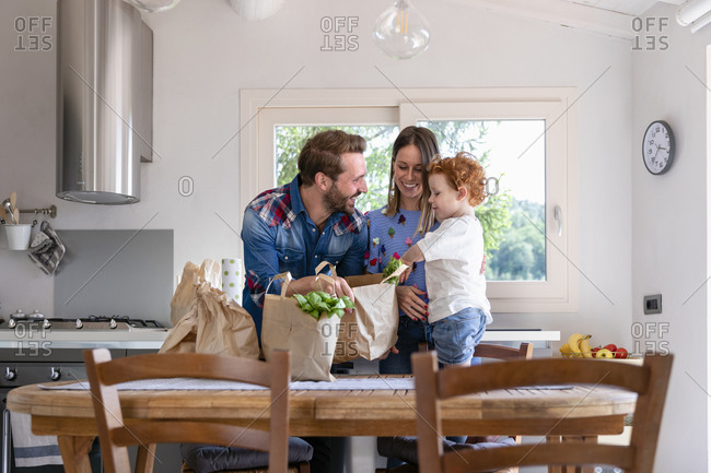 Happy family with groceries bag at dining table in kitchen