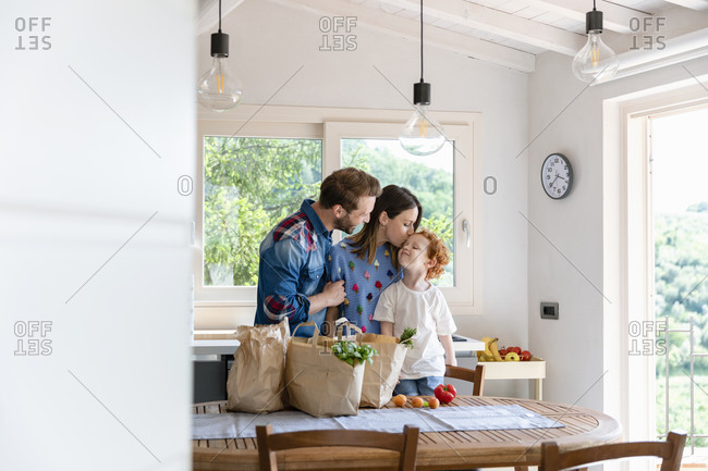 Smiling man looking at woman kissing son while standing at dining table with groceries in kitchen