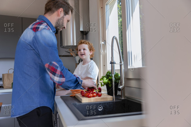 Cute boy looking at father washing cherry tomatoes in kitchen sink