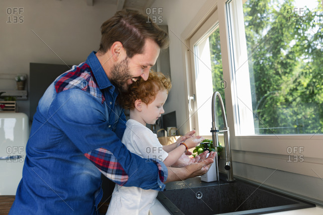 Smiling man washing hands with son in kitchen sink at home