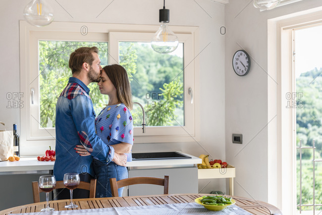 Man kissing woman while standing by dining table in kitchen at home
