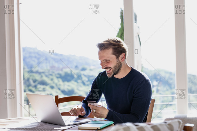 Smiling handsome man holding credit card while using laptop at dining table against window