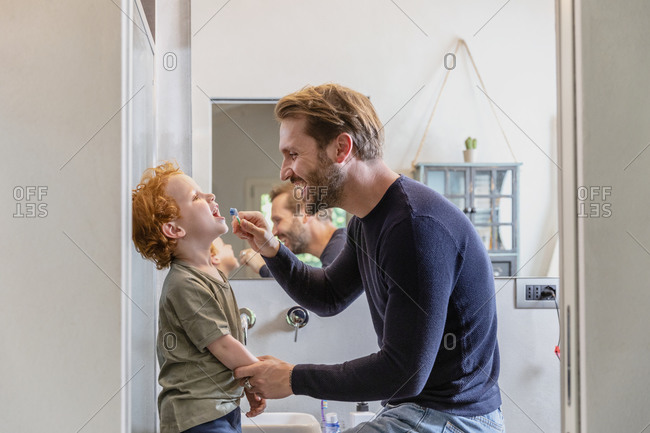 Happy man brushing son's teeth with toothbrush in bathroom at home