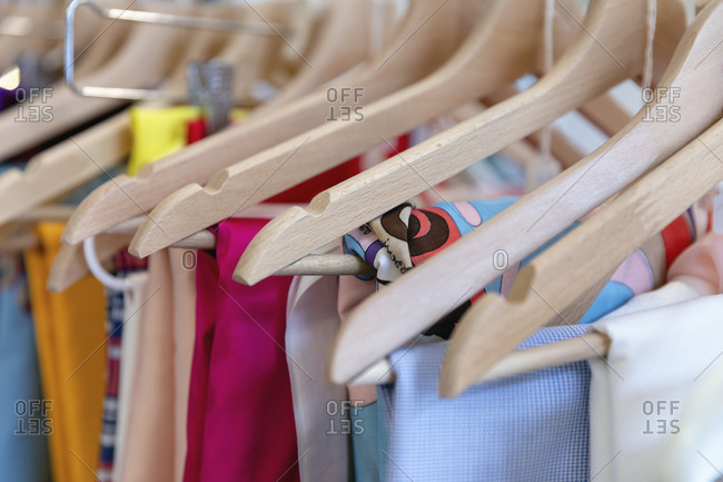 Close-up of wooden coat hangers on clothes rack at atelier