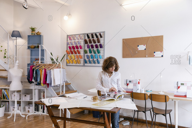 Female fashion entrepreneur looking at magazine while standing at workbench in design studio
