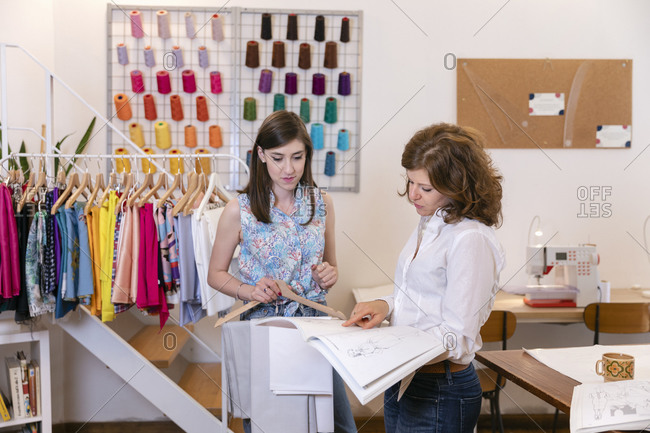 Female fashion designers discussing over book while working at studio