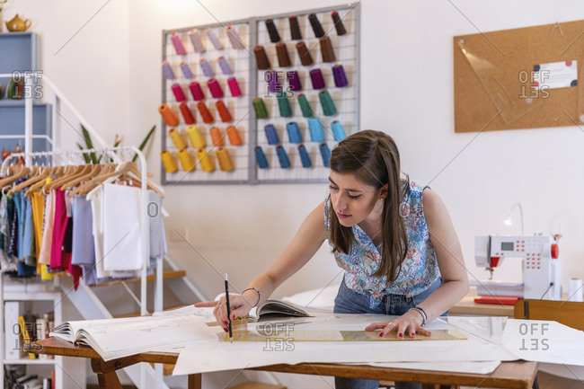 Beautiful young female designing trainee drawing on paper at workbench in studio