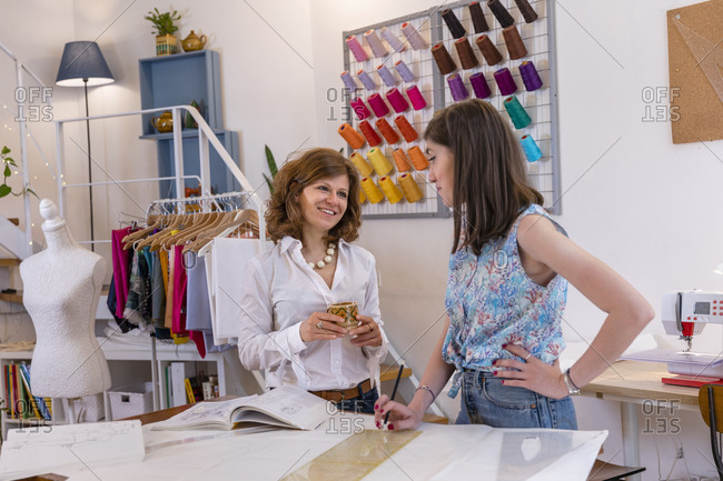 Smiling female fashion designer and young trainee discussing while standing at workbench in studio
