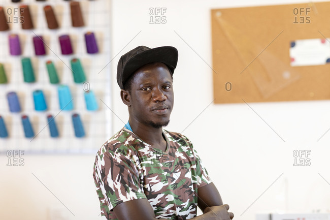 Confident young male fashion trainee standing with arms crossed at atelier