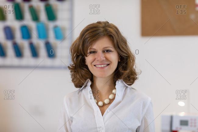 Smiling female entrepreneur at fashion designing studio