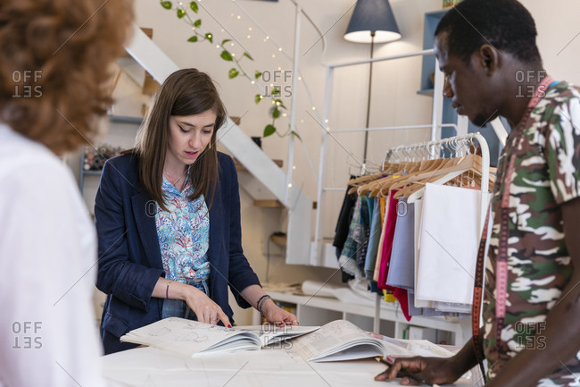 Young female trainee discussing over designs with coworkers at fashion studio