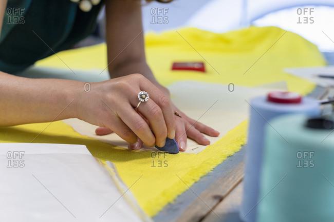Female fashion designer marking on yellow fabric at studio