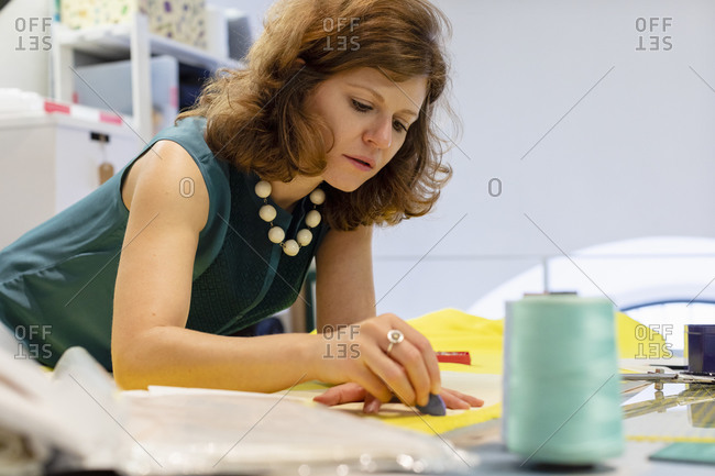 Fashion designer drawing on fabric with chalk at atelier