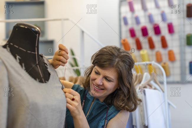 Smiling fashion designer sewing dress on dummy at design studio